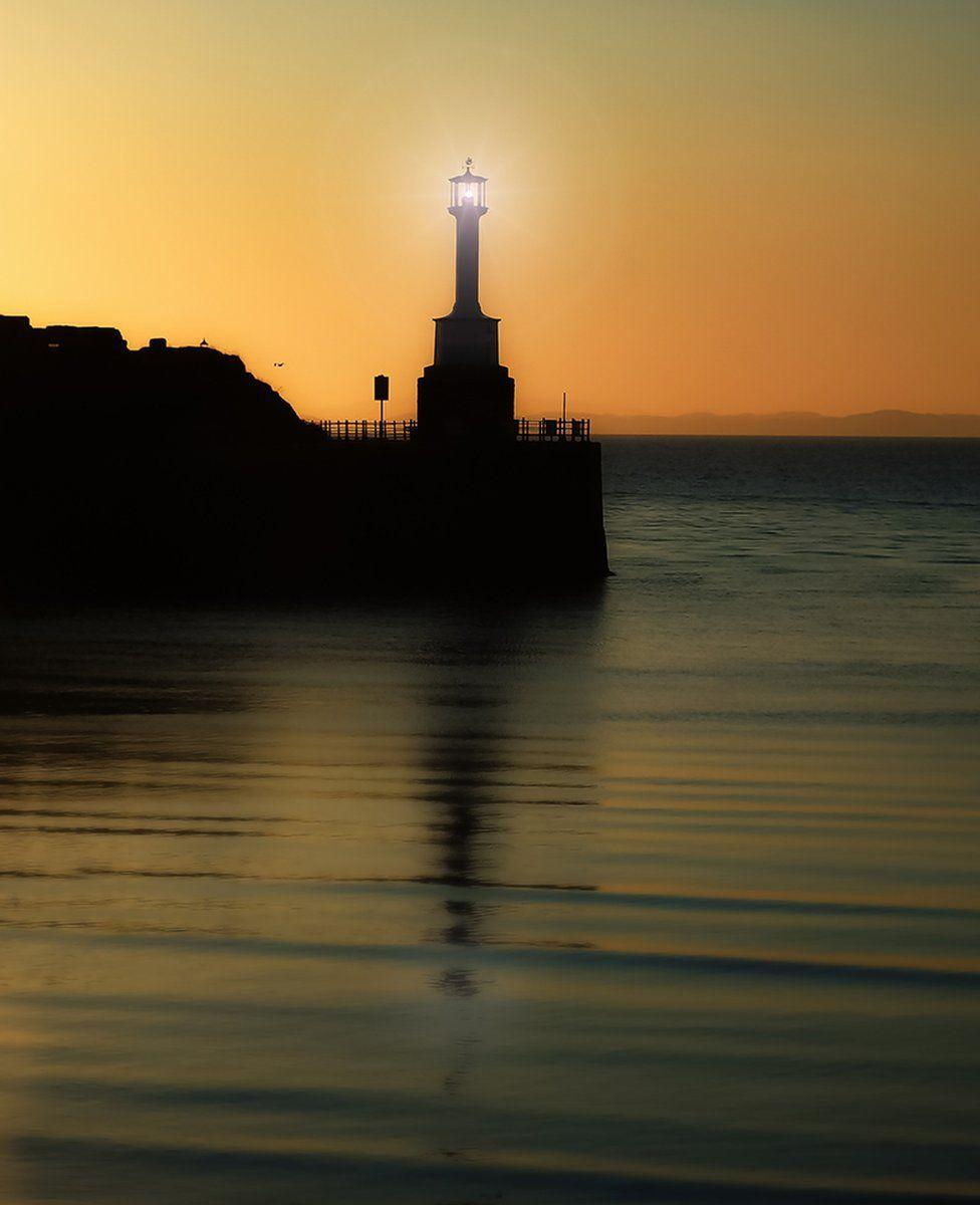 Sunset behind a lighthouse