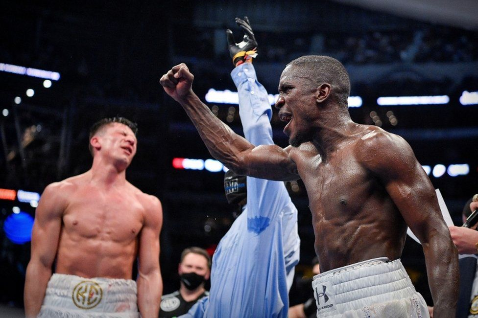 A boxer lifts his fist in jubilation as his opponent scrunches his face up in dismay.