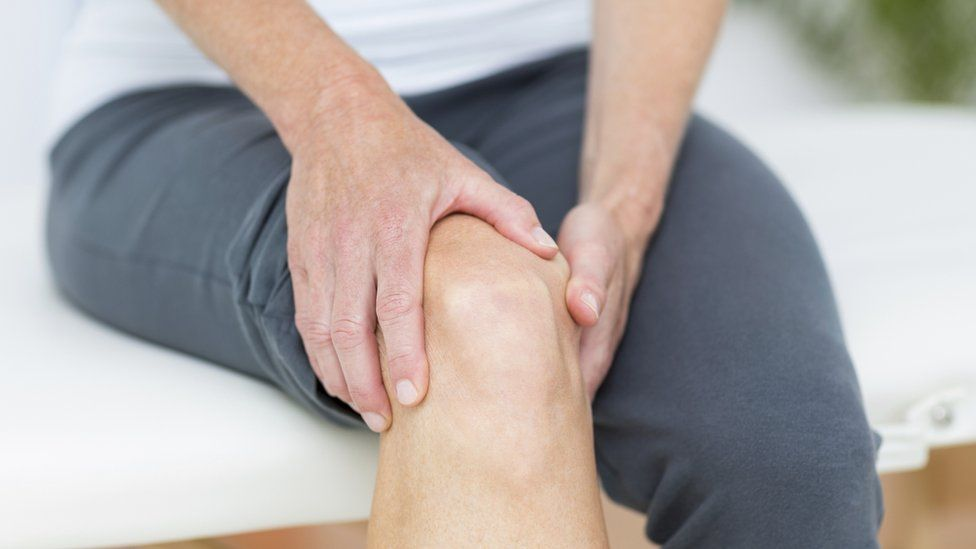 Man clutching knee