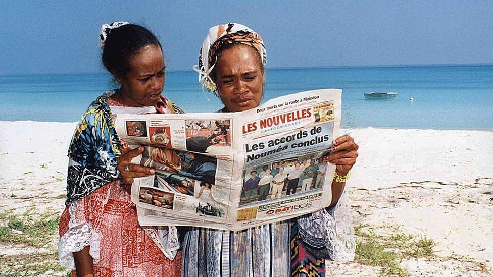 Two residents read about the historic signing of the Noumea Accord