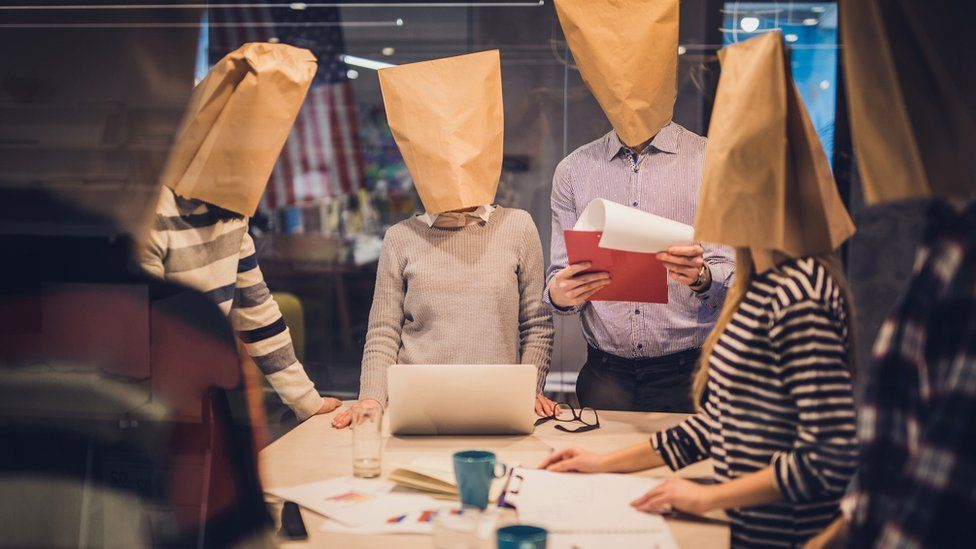 Workers with paper bags over their heads