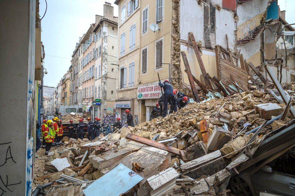 Firemen working and removing rubble at the site where two buildings collapsed, on November 5, 2018 in Marseille