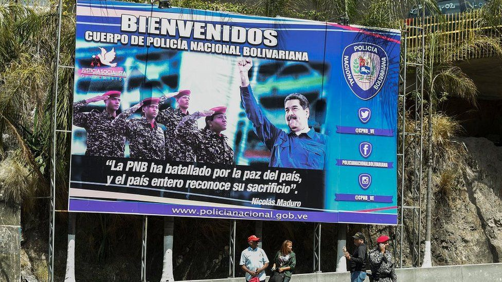 A poster of President Nicolas Maduro and security forces at the entrance of El Helicoide jail in Caracas