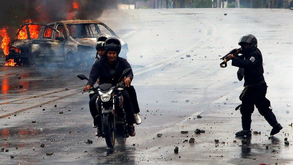 A riot police officer fires his shotgun towards two men during on a motorcycle on May 28, as the remains of a car burn brightly in the background