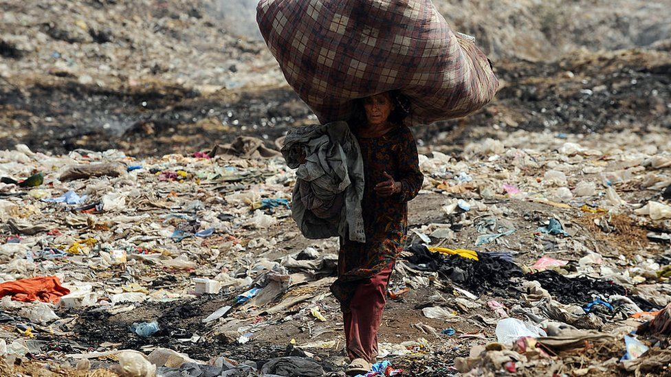 A Pakistani woman carries used clothing over her head