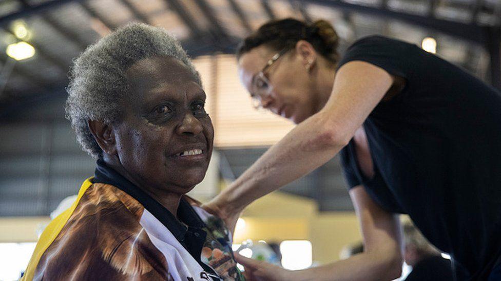 An elderly woman receives the AstraZeneca COVID-19 vaccine in Boigu Island, Australia