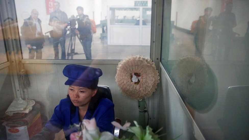 A North Korean worker sits in a booth at a wire factory