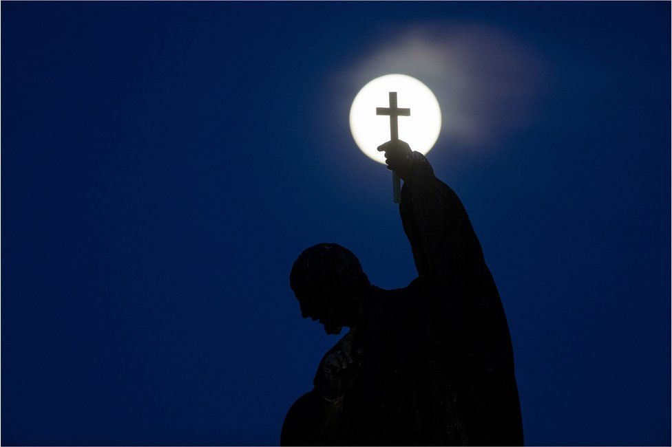 The pink supermoon rises behind a statue on Charles Bridge in Prague, Czech Republic