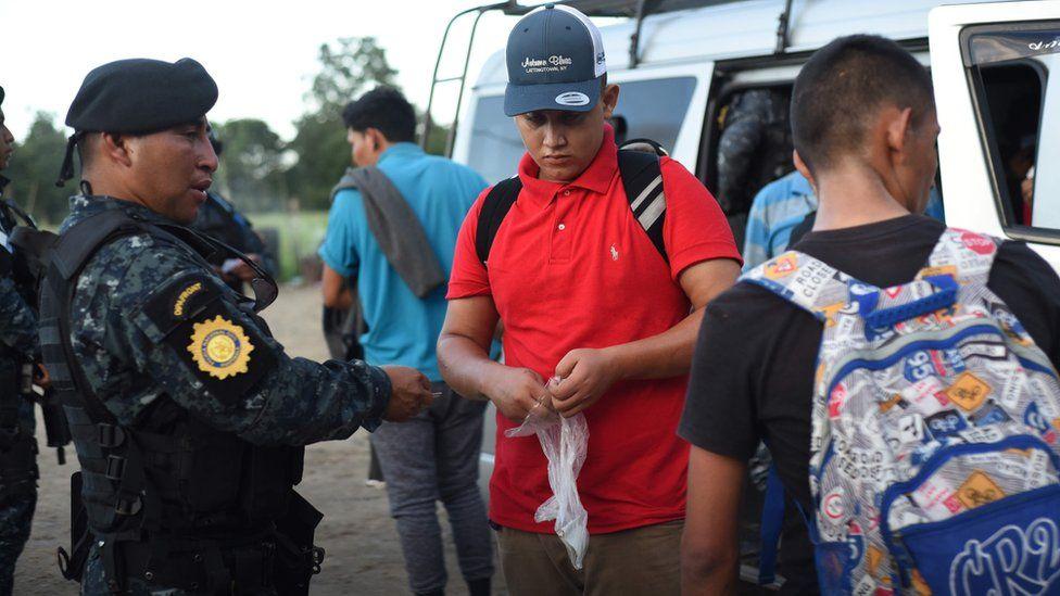 Guatemalan police agents check documents of Hondurans migrants at El Cinchado