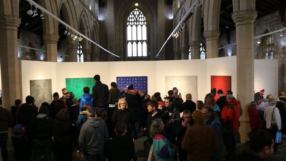 People looking at paintings to solve the clues