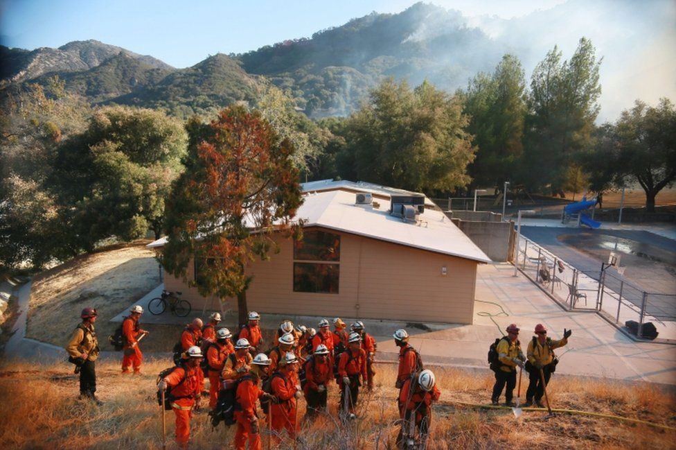 Fire crews prepare to clear brush along a fire line at the Salvation Army Camp on 10 November, 2018 in Malibu, California