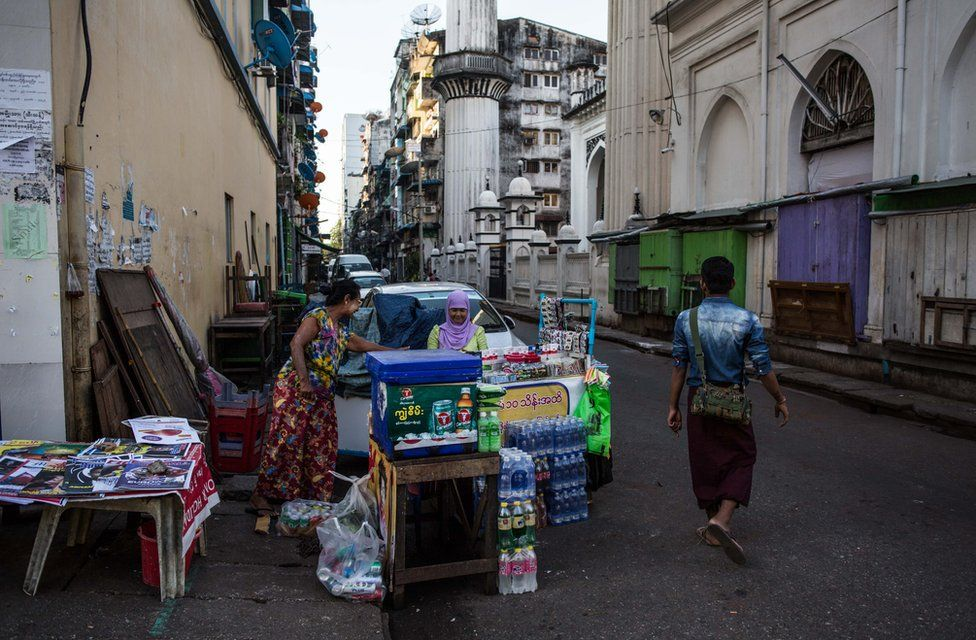 Thwarhairah exchanges money with her friend who sells newspapers next to her betel nut stand in downtown Yangon, Myanmar, November 14, 2015.