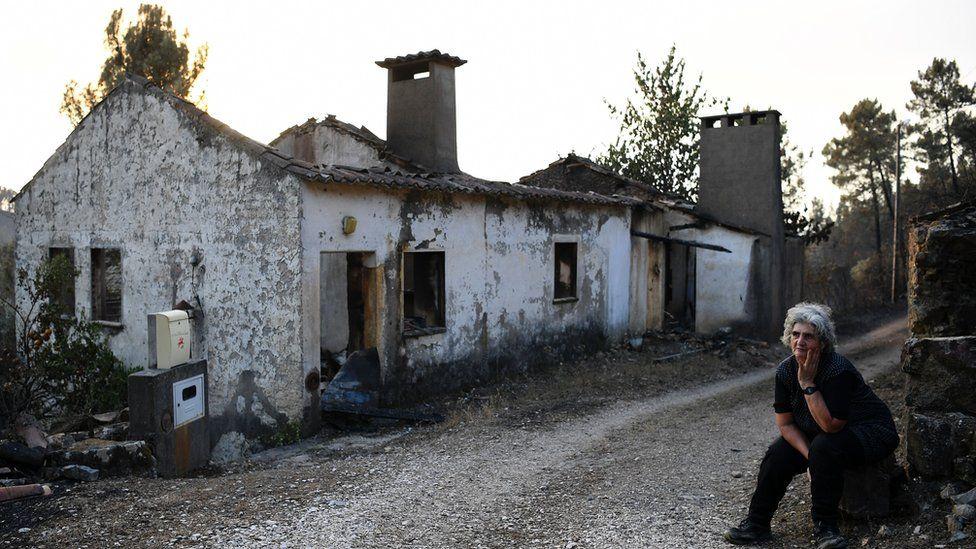 Maria Manuela Mendes sits beside her burnt house in Mendeira, near Cernache do Bonjardin, on June 19, 2017