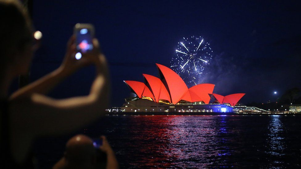 Spectators take photos of fireworks as they explode behind the Sydney Opera House as it glows red as part of celebrations for Chinese Lunar New Year of the pig, in Sydney