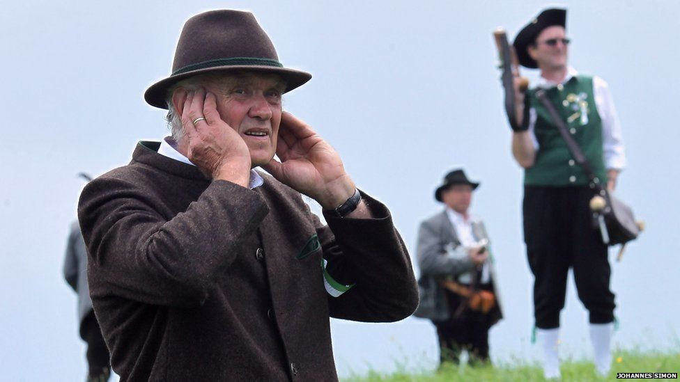 Traditional Bavarian boeller gunner protects his ears during a shoot