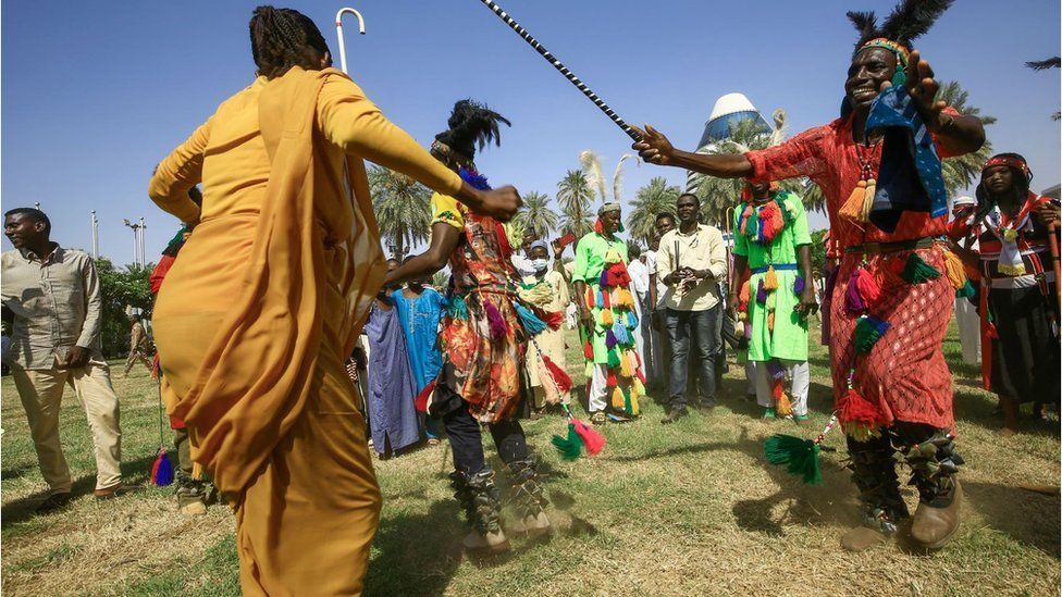 Lively photo of tribal dancers wearing colourful clothing. There is a man in a traditional red outfit with a head dress. He is dancing with a stick and his arms are open wide. A woman opposite him is wearing a yellow outfit and is also dancing. There is a crowd dressed in colourful clothing behind him.