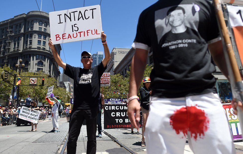 Jason Fairfield (L) holds up an anti-circumcision sign while marching with the Bay Area Intactivists along the Gay Pride parade route in San Francisco, California on Sunday, June, 26, 2016