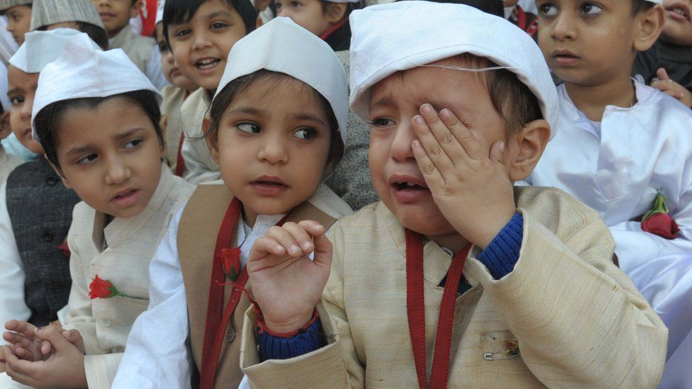 An Indian schoolboy (R) cries and he and schoolmates, dressed up as India's first prime minister Jawaharlal Nehru, pose during a photo event for Children's Day celebrations at a school in Amritsar