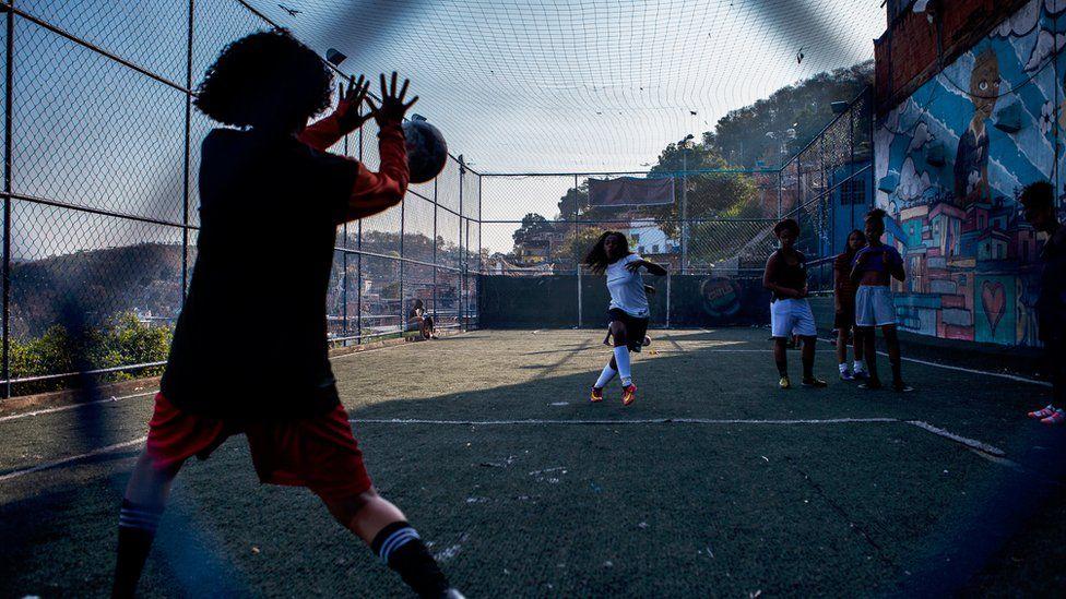 从目标后面看到,其中一名女子射门得分,守门员的等待手中,其他人在附近观看