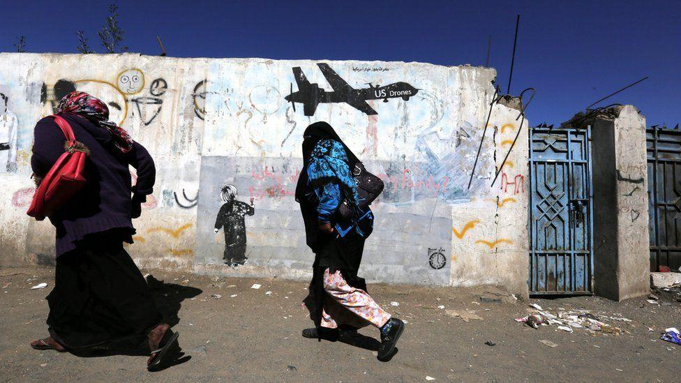 Yemeni women walk past graffiti protesting against US drone strikes on a wall in Sanaa, Yemen (24 December 2016)