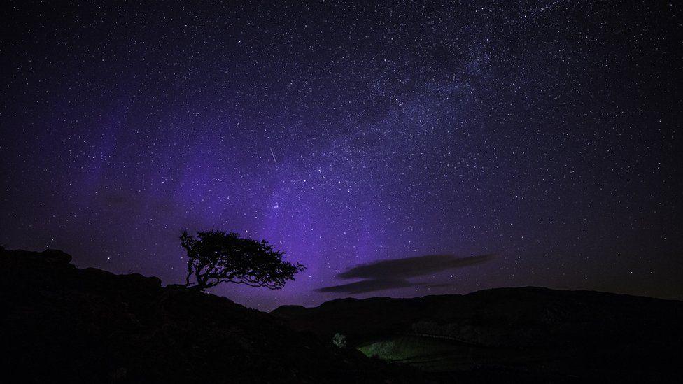A dark sky with stars and a purple light