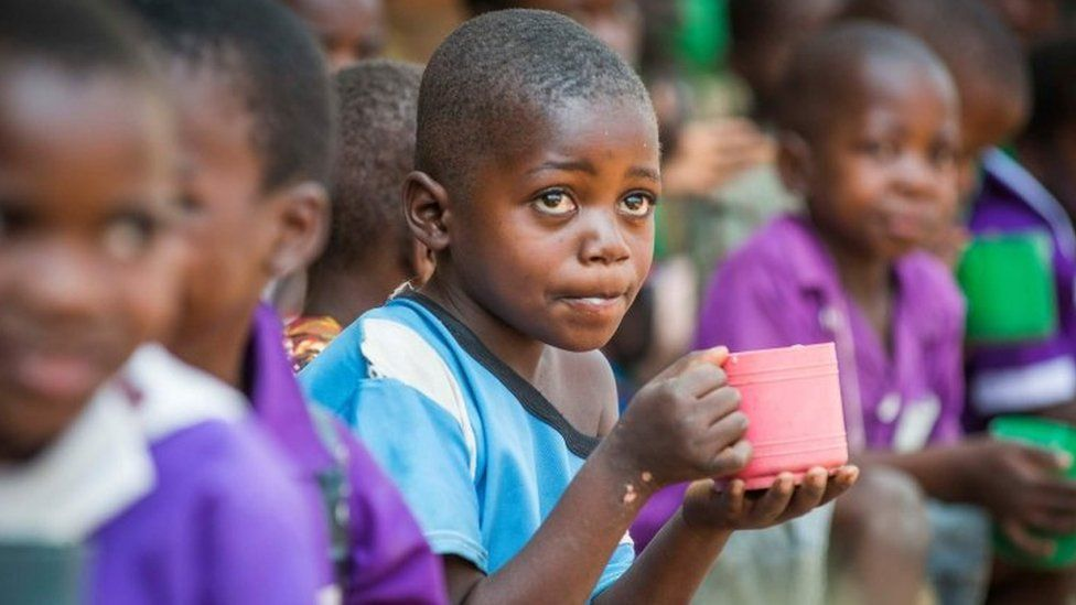 Child in Malawi being helped by Mary's Meals charity with food aid