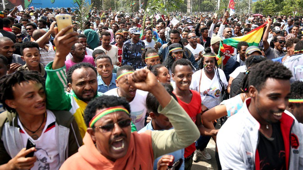 People celebrate during the welcoming ceremony of Eritrea's President Isaias Afwerki arriving for a three-day visit, at the Bole international airport in Addis Ababa, 14 July 2018