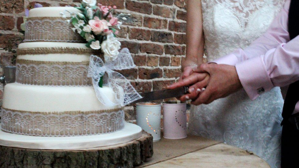 A newly-married couple cut their wedding cake