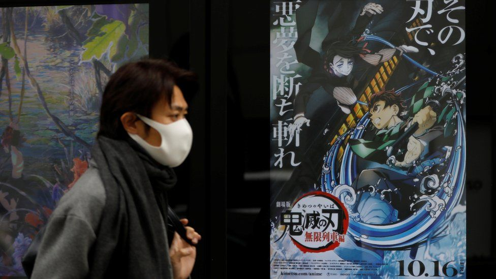 A man in Tokyo walking past a poster for Demon Slayer