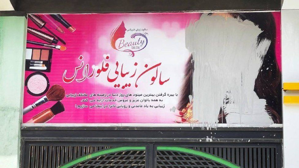 A billboard poster on which the face of a woman has been scratched out