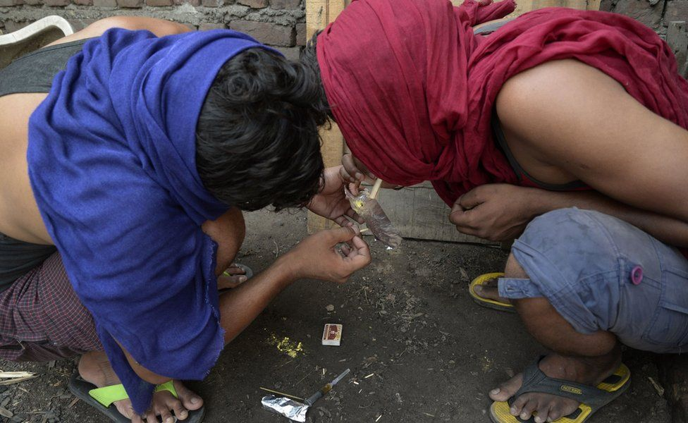 Indian youth inhale drugs on the outskirts of Jalandhar in the north western Punjab province on June 15, 2016