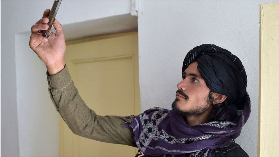 A Taliban fighter searches for a network signal for his mobile phone at a hospital.