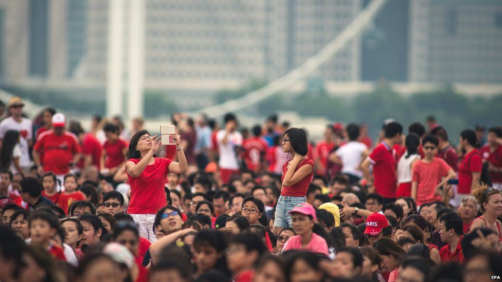 Spectators line the streets for independence day celebrations in Singapore