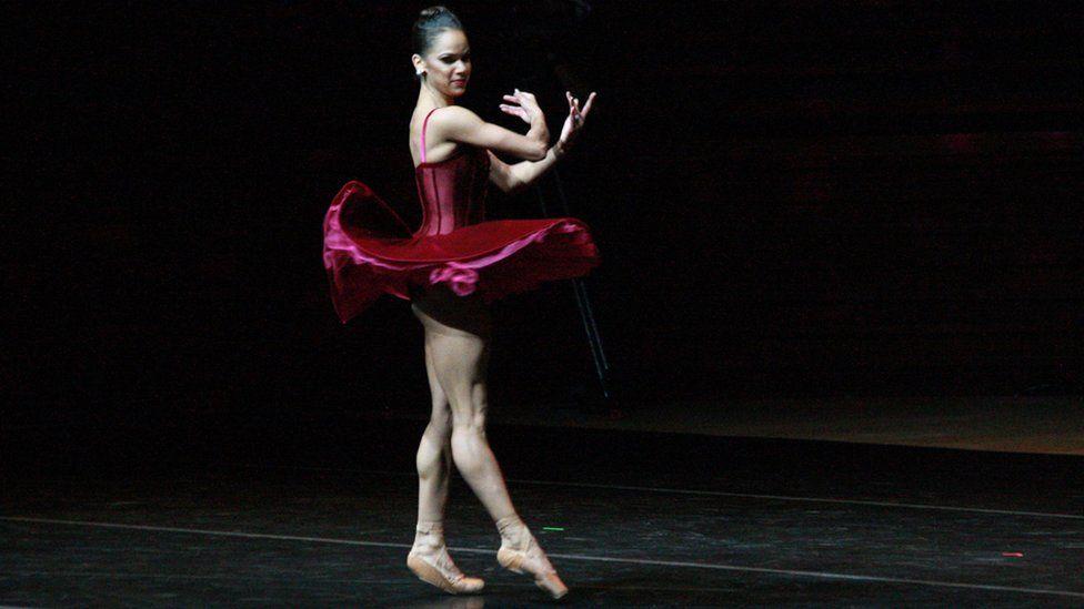 Misty Copeland dances wearing red velvet tutu