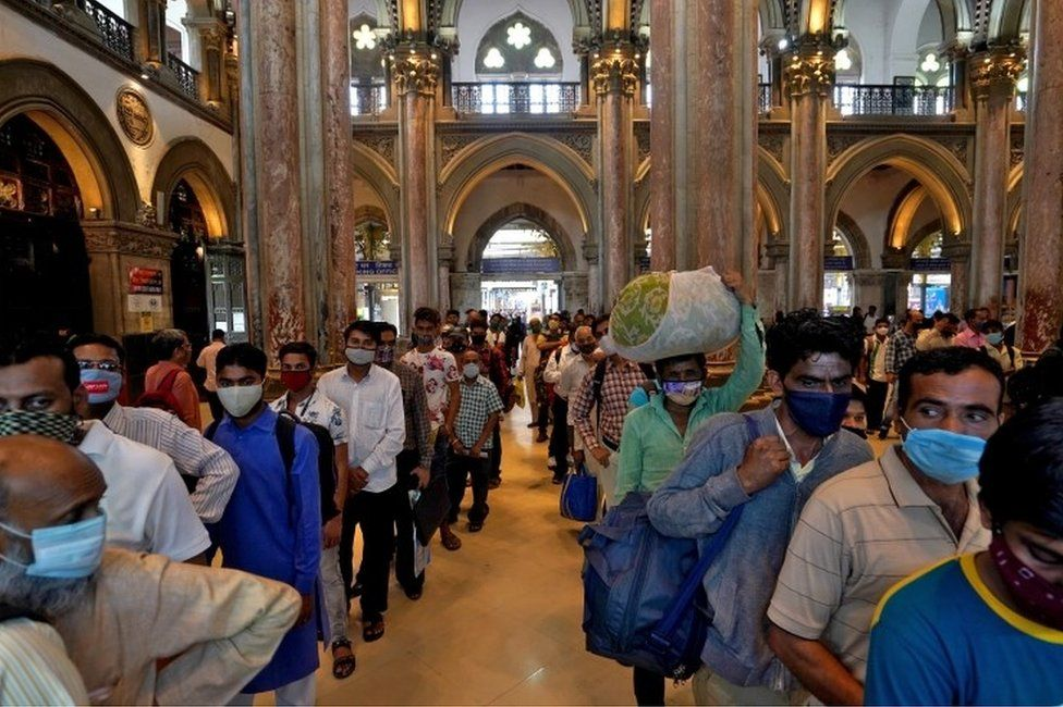 People wearing protective face masks wait in queues to buy train tickets at the Chhatrapati Shivaji Maharaj Terminus (CSMT) railway station after authorities resumed suburban train services for all commuters after it was shut down to prevent the spread of the coronavirus disease (COVID-19), in Mumbai, India, February 1, 2021.