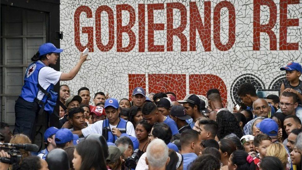 People queue to receive drums to collect water and water purification tablets from members of the Venezuelan Red Cross in Catia neighborhood in Caracas, Venezuela, on April 16, 2019.