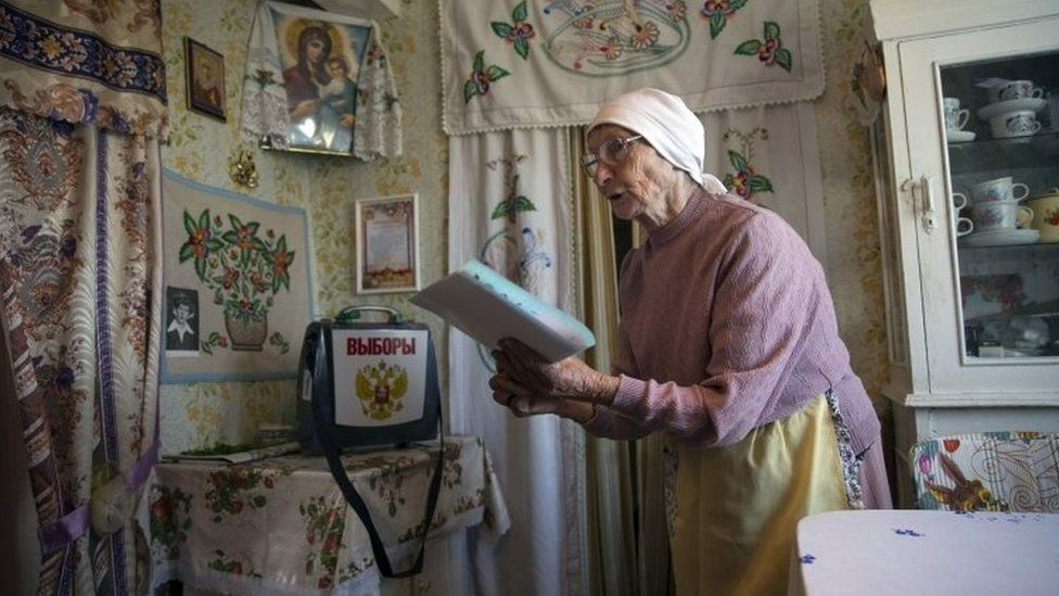 Galina Shalygina, 85, prepares to cast her ballot in a ballot box brought by election officials to villagers unable to travel to the polling station, in the village of Seltso, near Kostroma (13 September 2015)