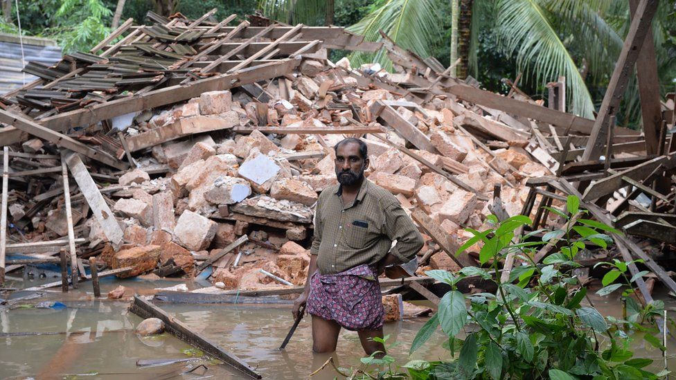 Ajith Prasad stands in front of the rubble of his house on the outskirts of Kozhikode