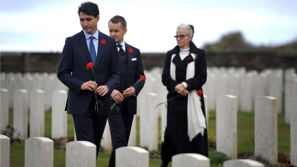 Canada's Prime Minister Justin Trudeau (L) and Canada's Veterans minister Seamus O'Regan (C) take part in a ceremony in tribute to Canadian soldiers killed during World War One at the Canadian National Vimy Memorial, 10 November 2018