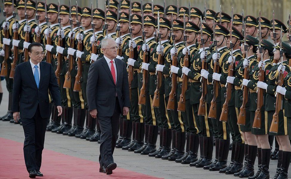 China's Premier Li Keqiang escorts Malcolm Turnbull past a line of Chinese military guards at an official welcome ceremony in Beijing in 2016