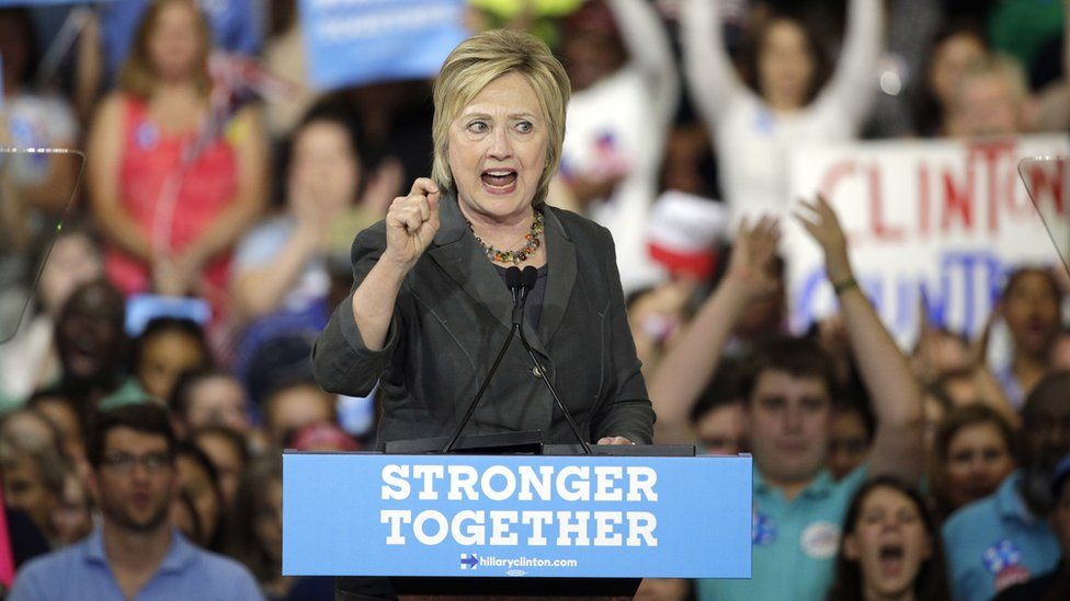 """Hillary Clinton at a rally, over a podium labelled """"stronger together"""""""
