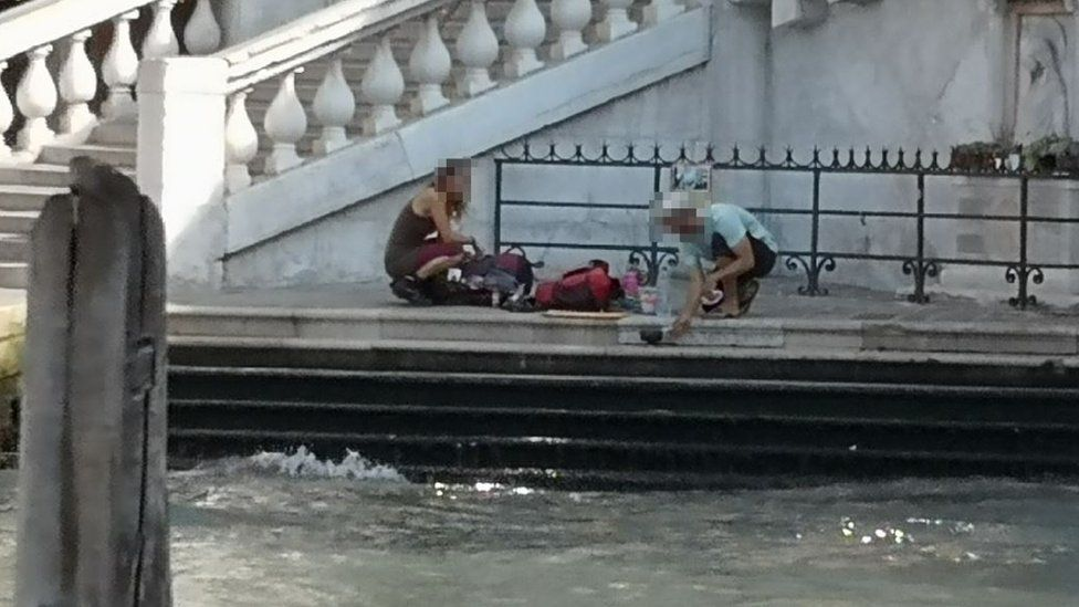 Tourists make coffee on side of river