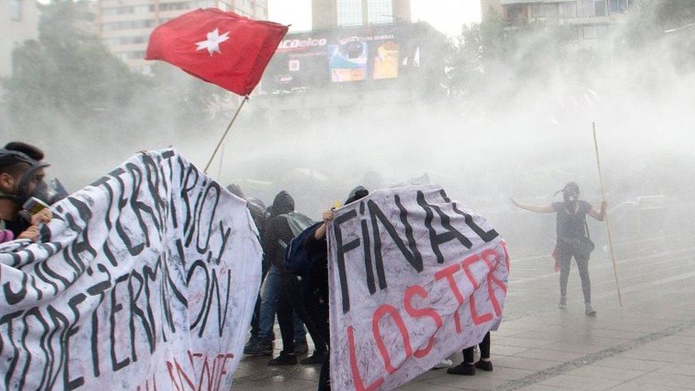 """Demonstrators are sprayed by the riot police with water during a protest by Mapuches indigenous people and human rights activists against the government as part of the Mapuches"""" ongoing fight for the recognition of their rights and demands, as well as for the recent killing by the police of a young Mapuche man, in Santiago, on December 14, 2018. -"""