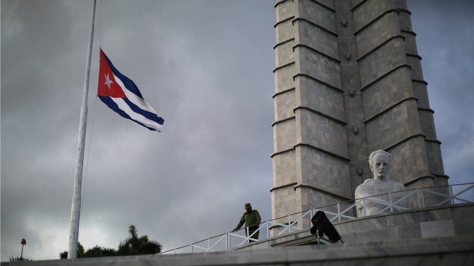 A soldier stands at Revolution Square as a Cuban flag flies at half mast