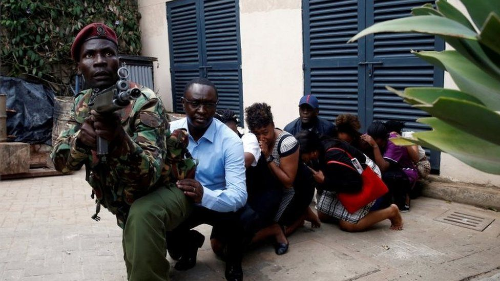 People are evacuated by a member of security forces at the scene where explosions and gunshots were heard at the Dusit hotel compound, in Nairobi, Kenya on 15 January 2019.