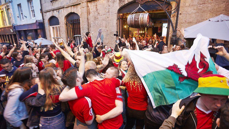 Fydd yna ddathlu fel hyn ar strydoedd Caernarfon ym mis Gorffennaf? // A street in Caernarfon erupts as Wales go on in the Euro 2106 championship