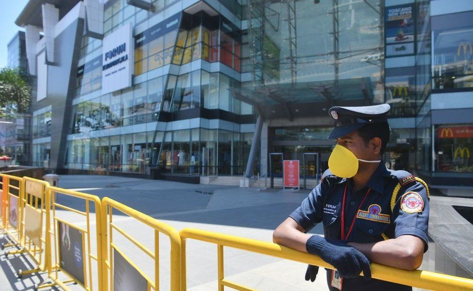 A security personnel stands guard in front of a closed shopping mall amid concerns over the spread of the COVID-19 novel coronavirus, in Bangalore on March 16, 2020.