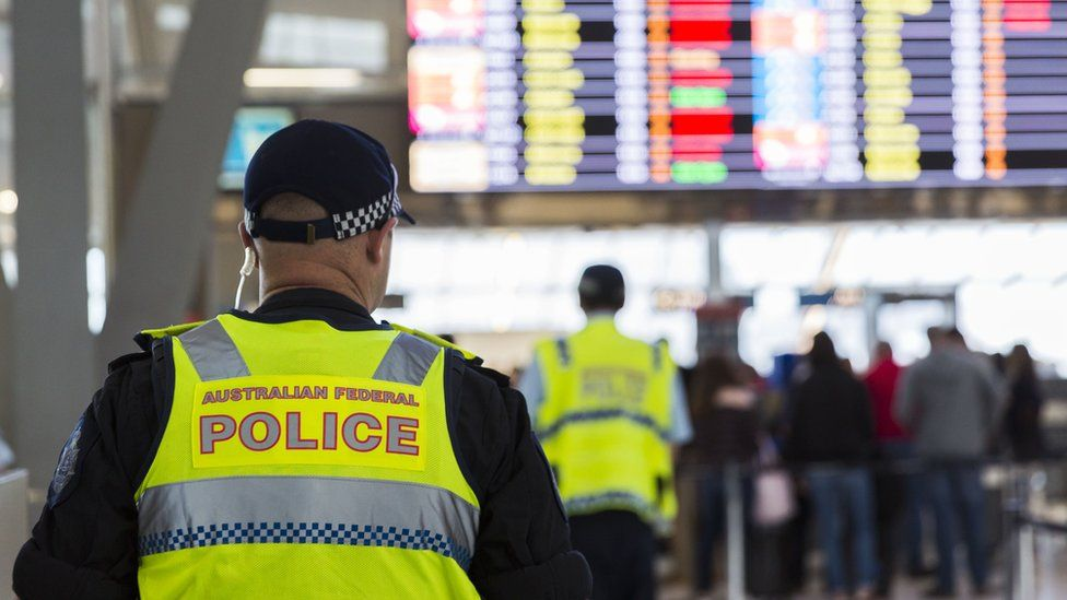 A police officer in a fluoro yellow vest faces a flight departure screen in Sydney Airport