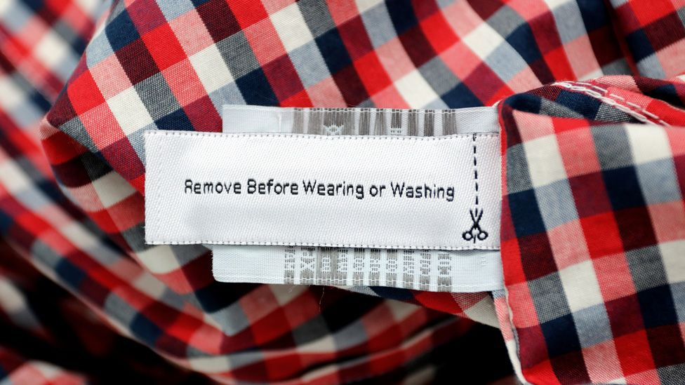 """A """"Remove before wearing and washing"""" RFID tag on red checked shirt"""