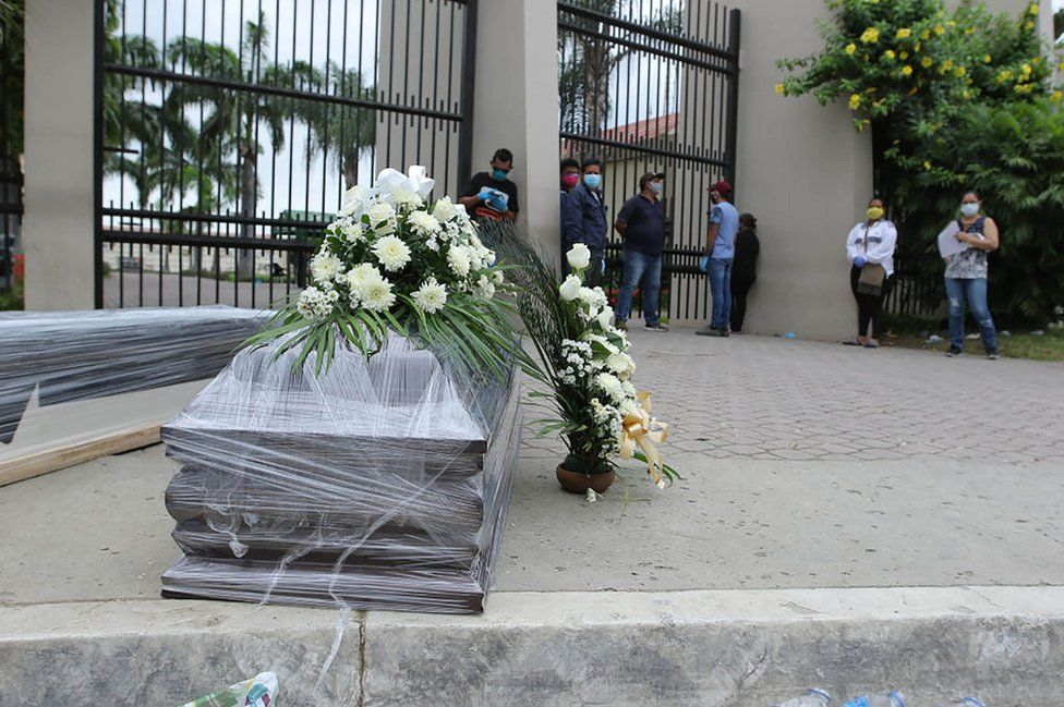 Relatives of a dead person line up for a funeral outside the Durán cemetery